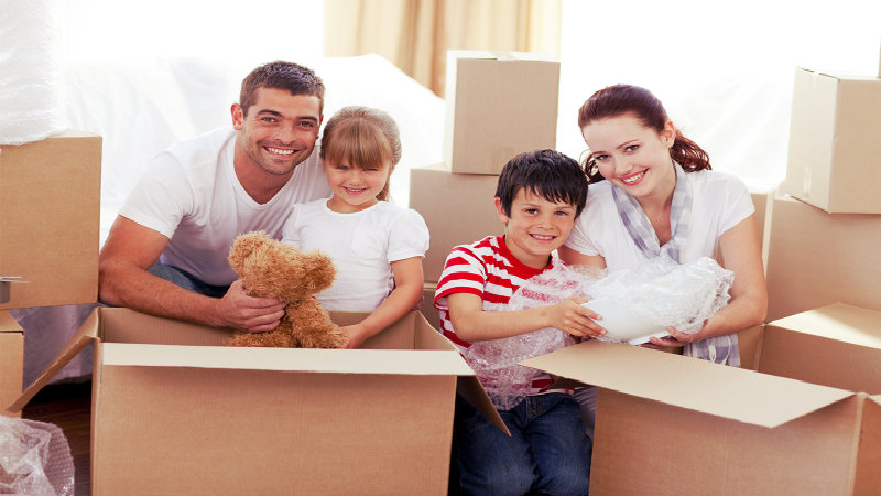 young family of four carrying boxes to the moving van
