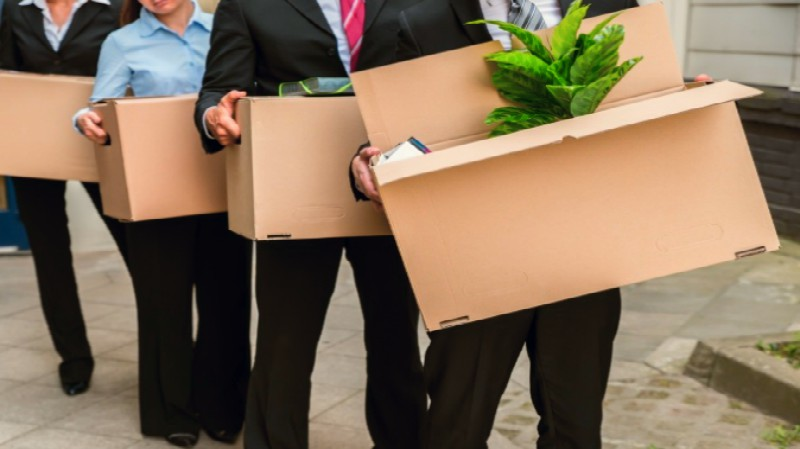 young couple sitting on couch with boxes all around