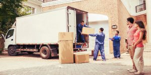 young woman helping elderly couple pack their belongings for the move