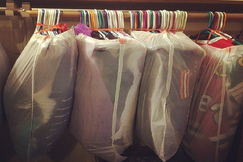 young couple happily carrying boxes out of their house