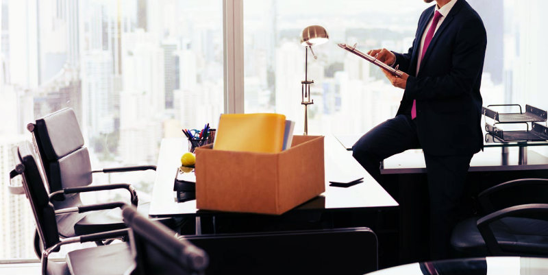 cropped image of a man sitting on office table with packing box kept on it