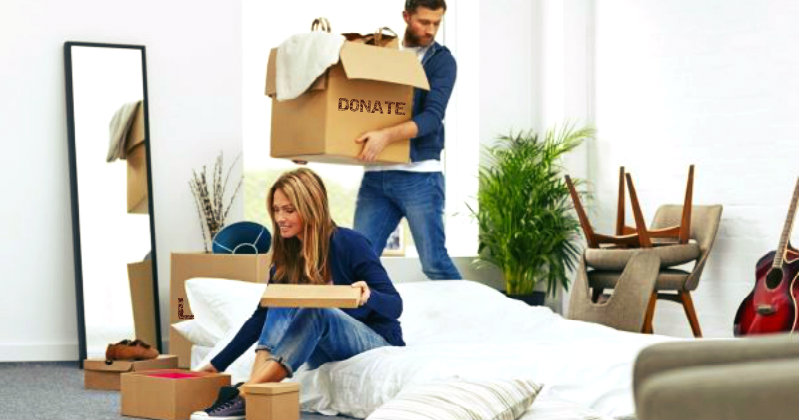 Man carrying a box of items to be donated and woman sitting on floor and sorting things