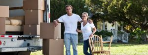 a couple is posing with a truck loaded with cardboard boxes