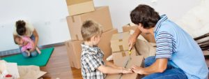 young man is packing a cardboard box with his child