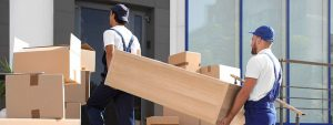 young professionals loading furniture inside a moving truck