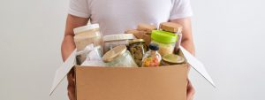 young man holding a cardboard box full of food supplies