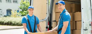 Young professionals loading household into a moving truck
