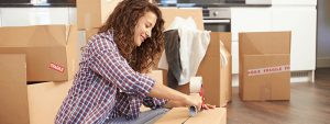 young woman packing household items for a relocation