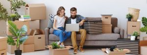 young couple sitting on a couch and searching for something online